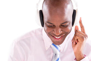 Business man listening to music with headphones - isolated over white